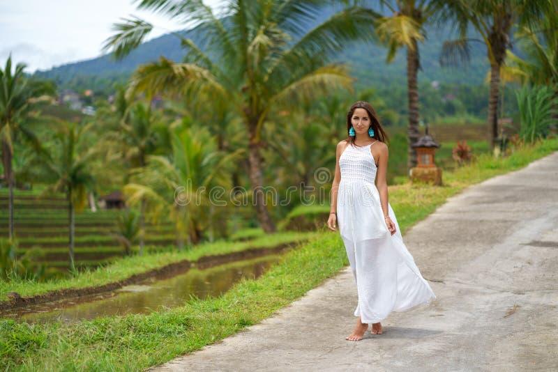 Härlig brunbränd kvinna i den vita klänningen som poserar anseende på vägen I bakgrunden är palmträd och annan tropisk veg royaltyfri fotografi