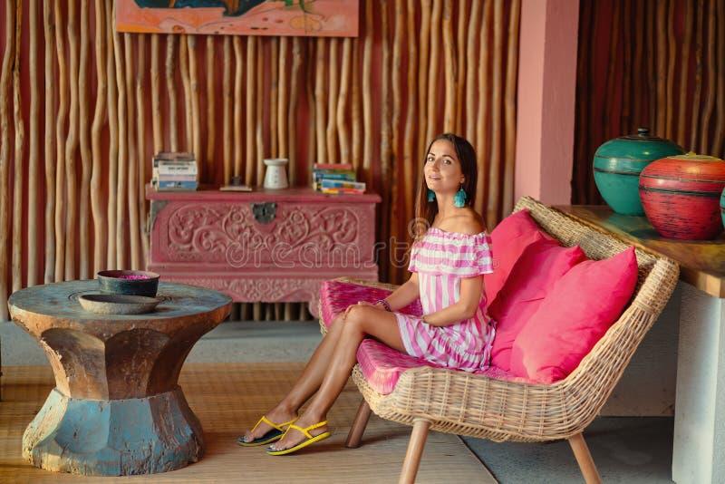Härlig brunbränd kvinna som sitter på en rosa soffa och posera Inre i etnisk stil arkivfoto