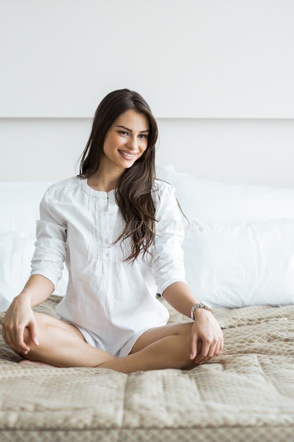 Härlig brunett i en vit skjortaskräddareplats som poserar på en säng royaltyfri foto