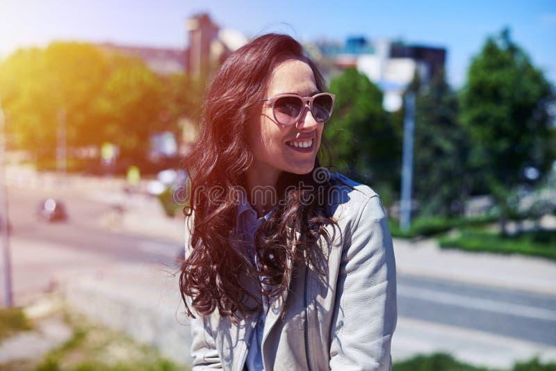 Härlig brunett i solglasögon som tycker om sikt av staden arkivfoto