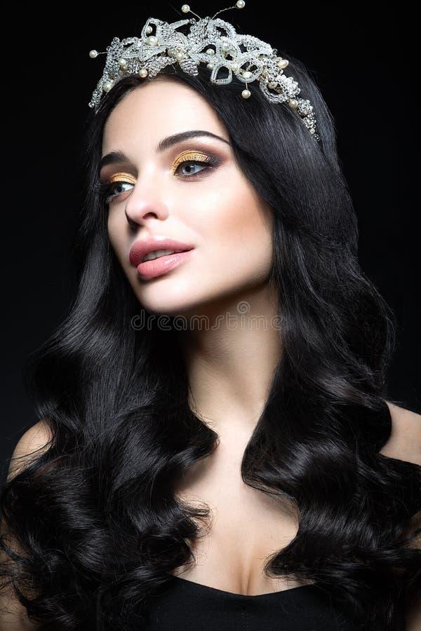 Härlig brunett med en krona av ädelstenar, krullning och aftonmakeup Härlig le flicka royaltyfria bilder