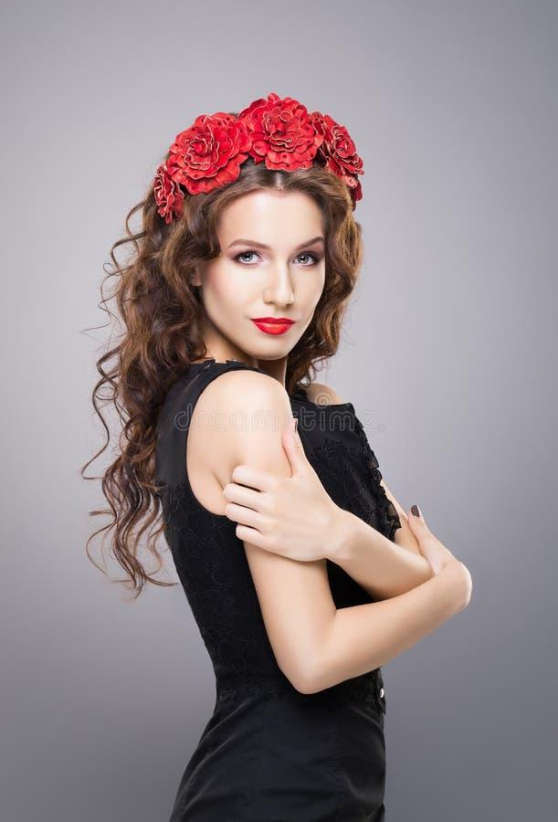 Härlig brunett med en ljus röd läppstift som bär en blommahuvudbindel arkivfoto