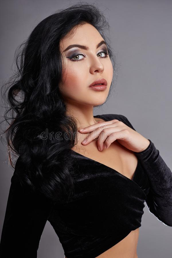 Härlig brunett med svart lockigt hår, det perfekta diagramet och stora ögon Svart överkant och jeans på kvinnakroppen Grå färgbak royaltyfri fotografi