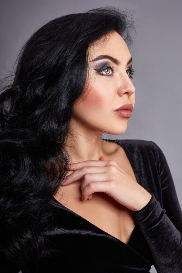 Härlig brunett med svart lockigt hår, det perfekta diagramet och stora ögon Svart överkant och jeans på kvinnakroppen Grå färgbak arkivfoto