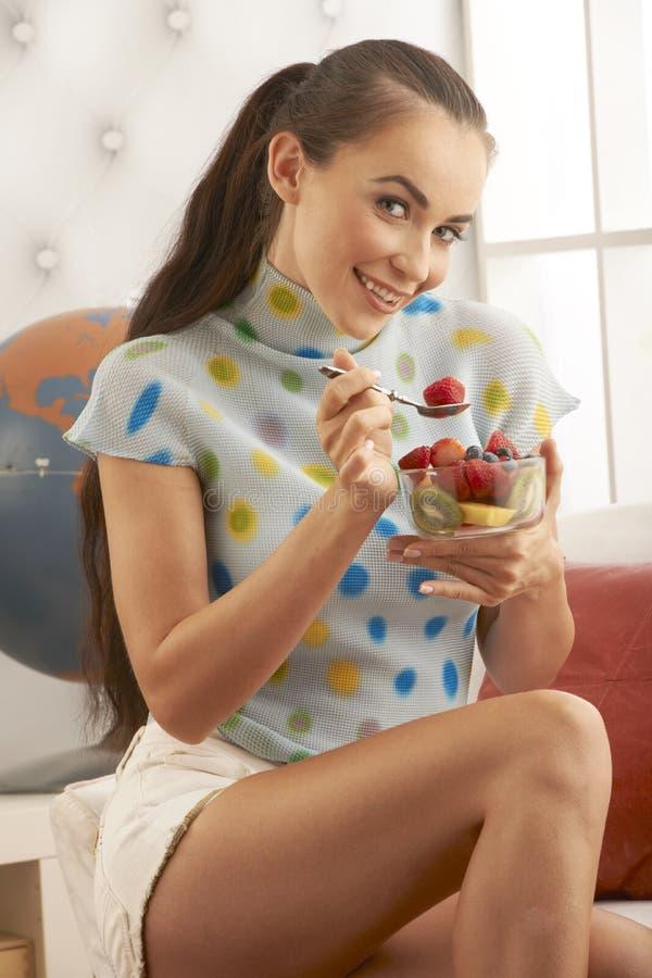 härlig brunett som äter frukt royaltyfria bilder