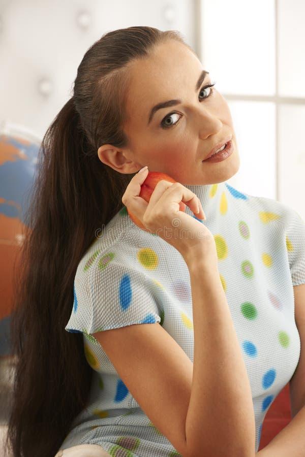 härlig brunett som äter frukt royaltyfri foto