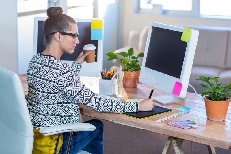 Härlig brunett som arbetar med digitizer- och innehavkaffe arkivfoton