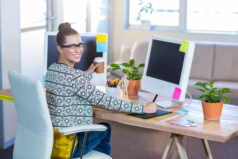 Härlig brunett som arbetar med digitizer- och innehavkaffe royaltyfria bilder