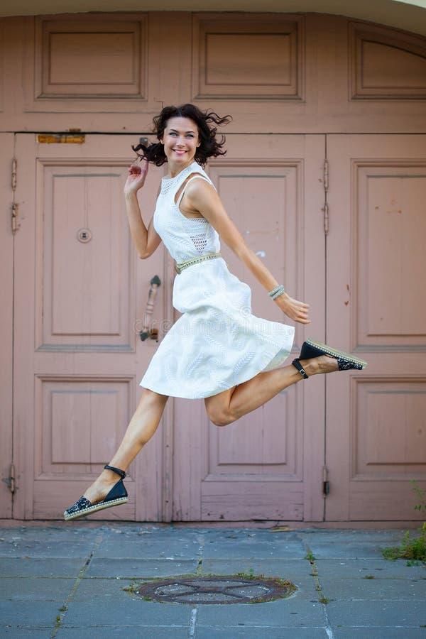 Härlig brunett som hoppas i en vit klänning royaltyfria foton