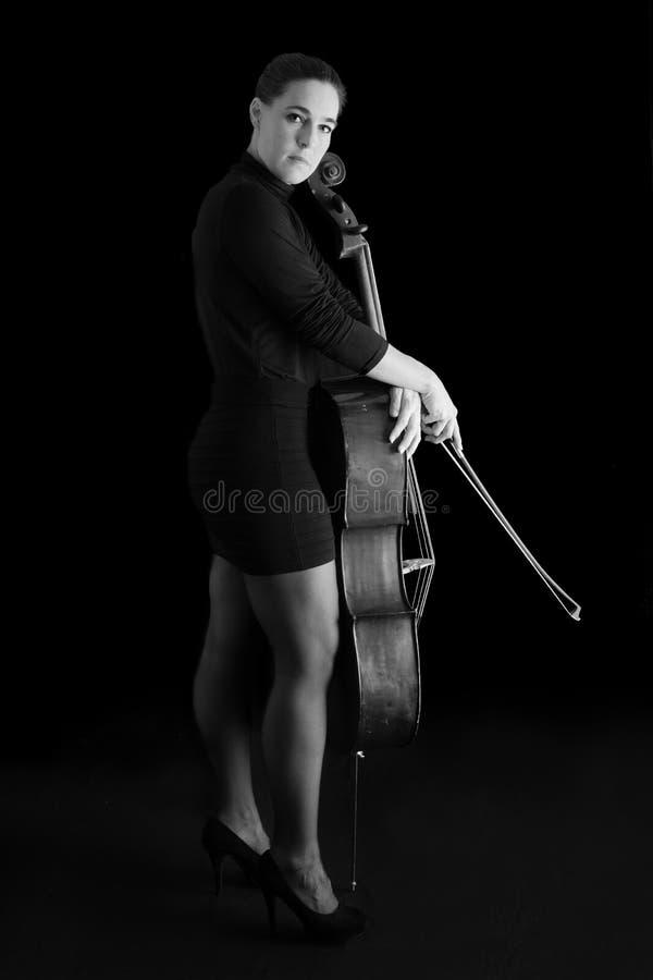 Härlig brunett som spelar violoncellen med selektivt ljus i svart D royaltyfri fotografi