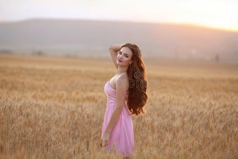Härlig brunett som tycker om i vetefält på solnedgången utomhus- så royaltyfri fotografi