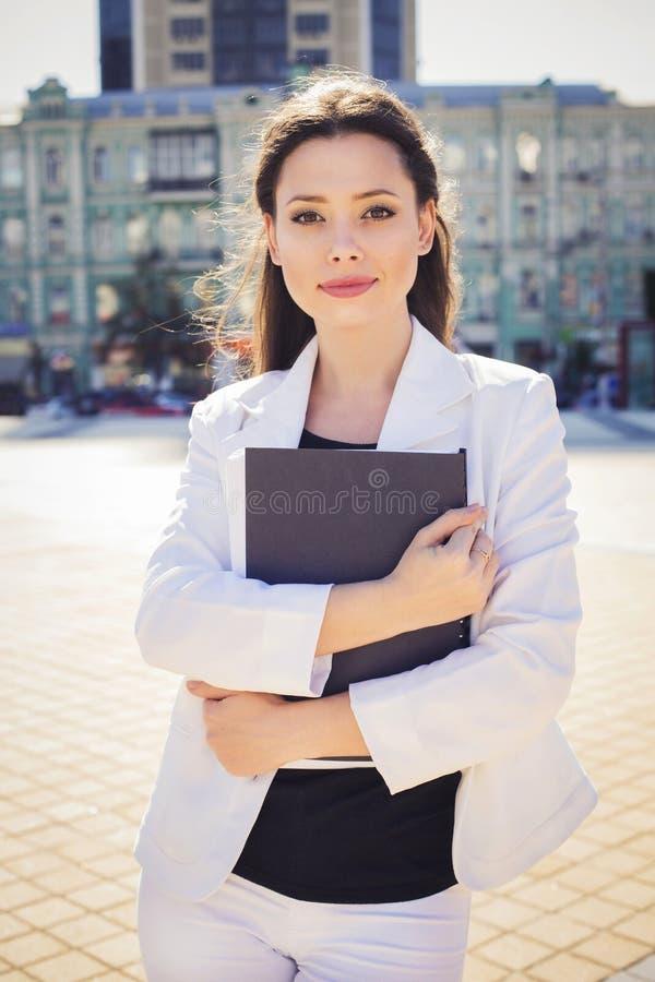 Härlig brunettaffärskvinna i den vita dräkten med mappen av dokument i hennes händer utomhus arkivbilder
