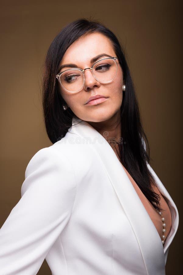 Härlig brunettaffärskvinna som poserar bärande exponeringsglas arkivbilder