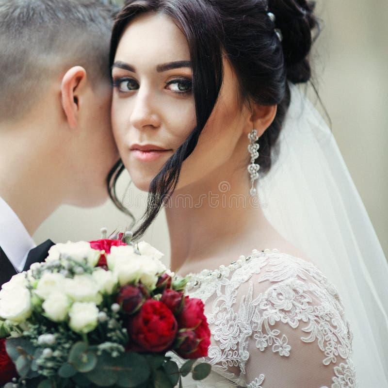 Härlig brunettbrud med bröllopbuketten som ler, medan kram arkivfoton