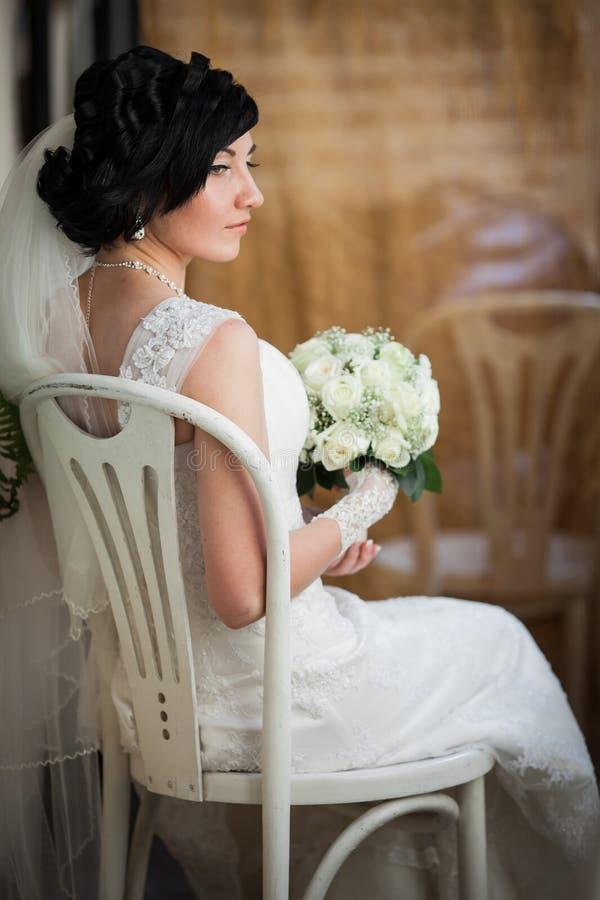 Härlig brunettbrud med buketten för vita rosor i elegant dre royaltyfria bilder
