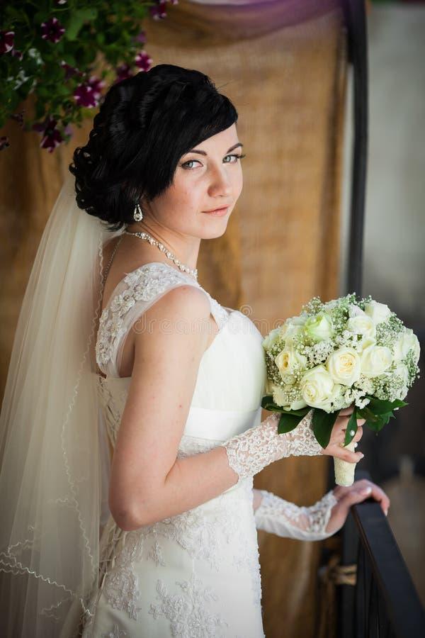 Härlig brunettbrud med buketten för vita rosor i tappningdre royaltyfri bild