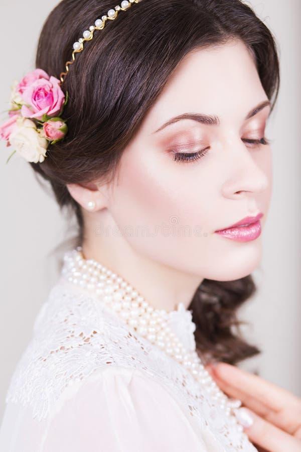 Härlig brunettbrud som ler med naturliga smink- och blommarosor i hennes frisyr royaltyfria foton