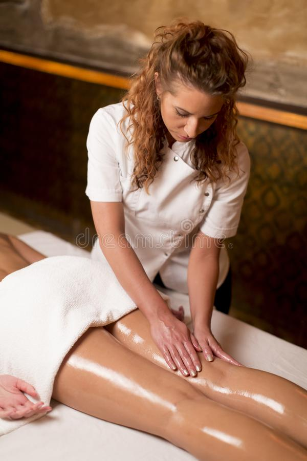 Härlig brunettbrunnsortkvinna som får massage på handduken i brunnsortsal arkivbilder