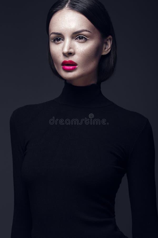Härlig brunettflicka i en svart klänning, ett rakt hår och en moderiktig makeup Glamourskönhetframsida royaltyfria bilder