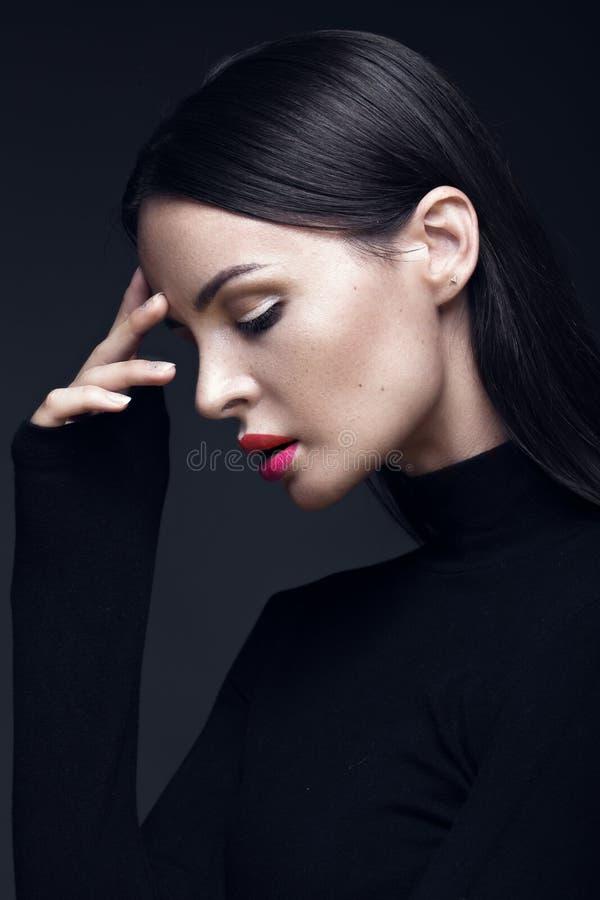 Härlig brunettflicka i en svart klänning, ett rakt hår och en moderiktig makeup Glamourskönhetframsida arkivbild
