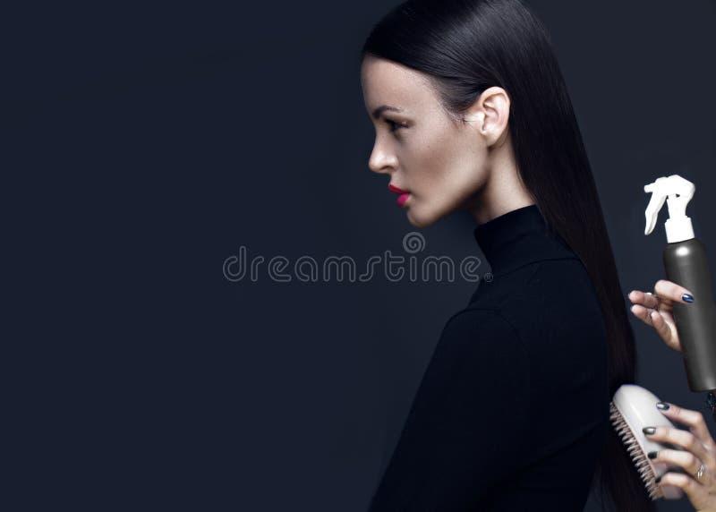 Härlig brunettflicka i en svart klänning, ett rakt hår och en moderiktig makeup Glamourskönhetframsida royaltyfria foton