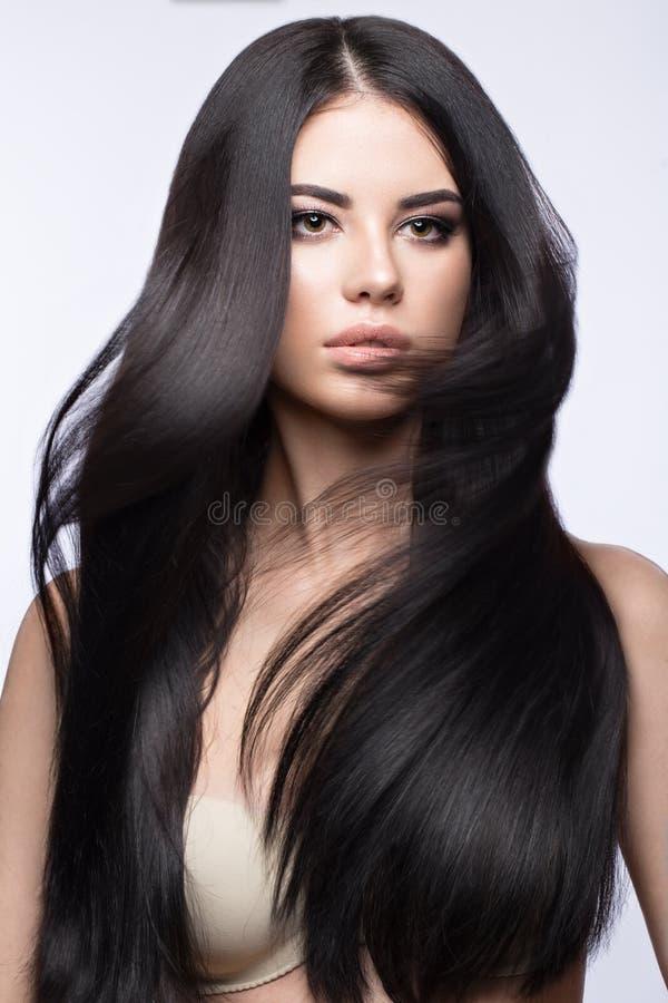 Härlig brunettflicka i flyttning med ett perfekt slätt hår och klassiskt smink Härlig le flicka arkivbild