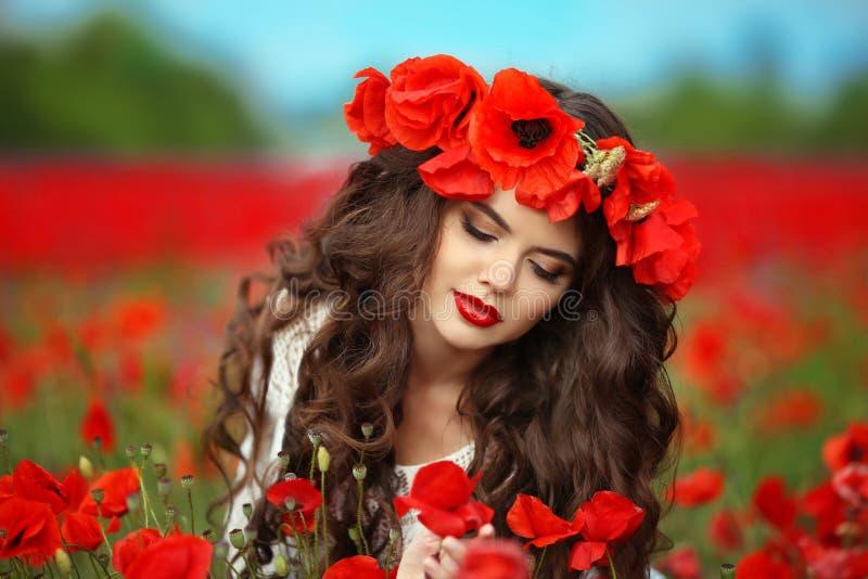 Härlig brunettflicka i röd backgr för natur för vallmoblommafält royaltyfri fotografi