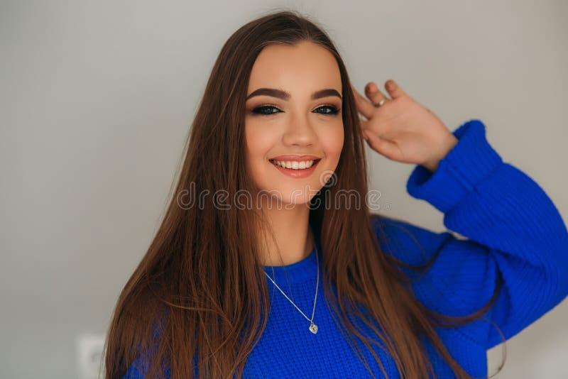 Härlig brunettflicka med ett älskvärt leende i en blå blus som poserar för en fotograf och visar henne makeup royaltyfria bilder