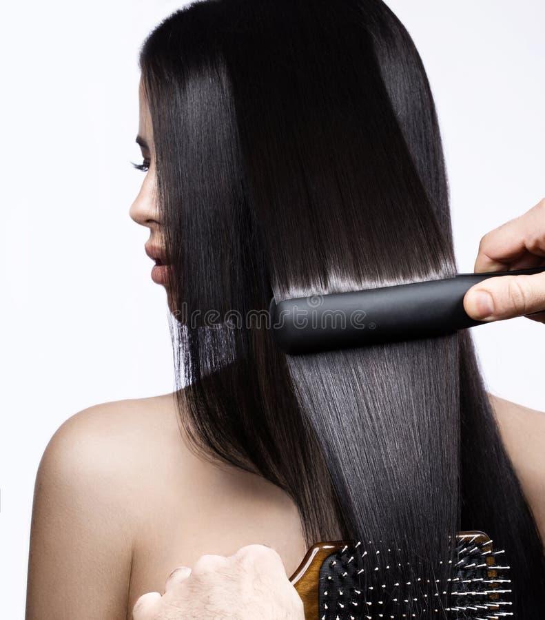 Härlig brunettflicka med ett perfekt slätt hår, krulla och ett klassiskt smink Härlig le flicka fotografering för bildbyråer