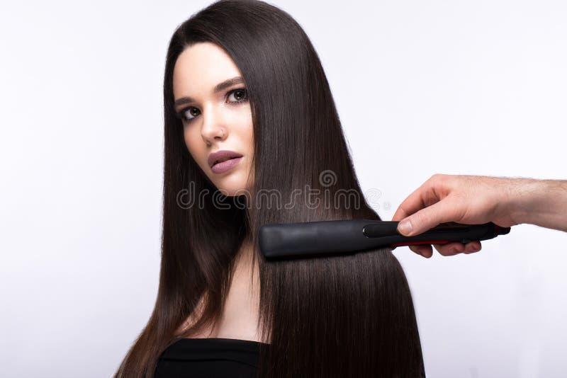 Härlig brunettflicka med ett perfekt slätt hår, krulla och ett klassiskt smink Härlig le flicka royaltyfri bild