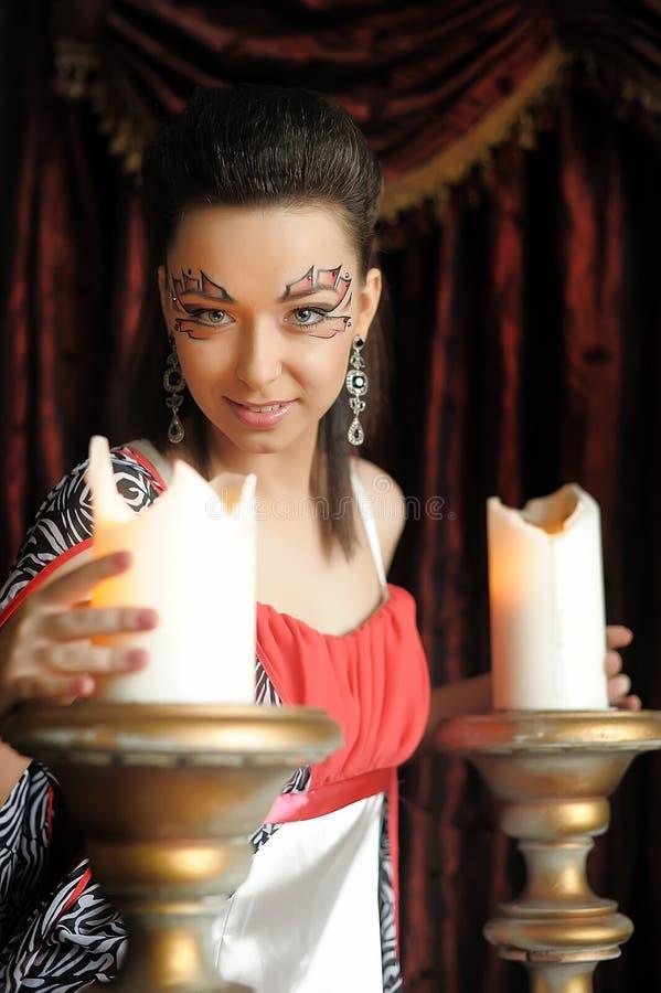 Härlig brunettflicka med idérikt smink nära de stora stearinljusen royaltyfri foto