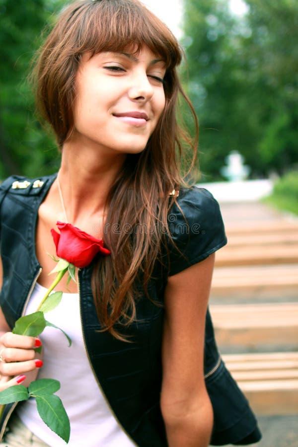 Härlig brunettflicka med knoppen av rosen arkivbild