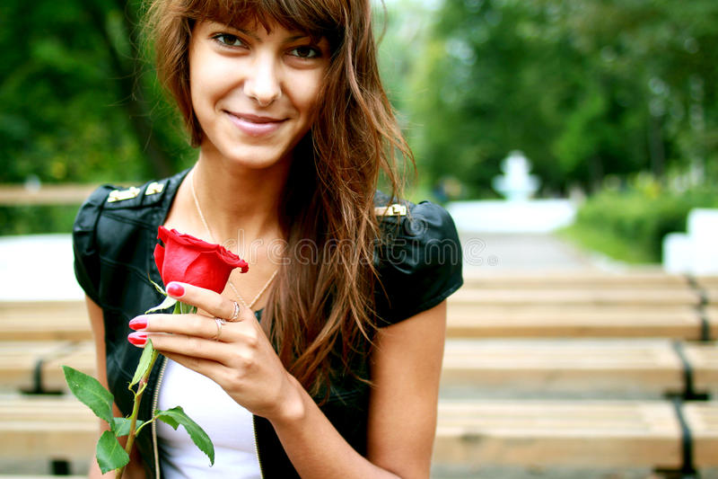 Härlig brunettflicka med knoppen av rosen arkivfoto