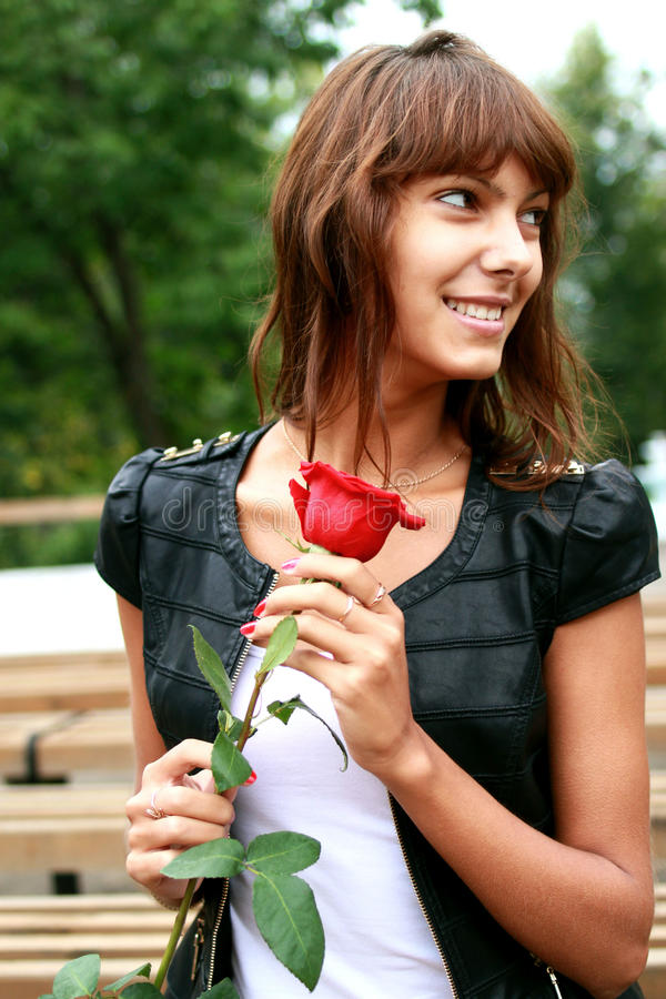 Härlig brunettflicka med knoppen av rosen royaltyfri bild