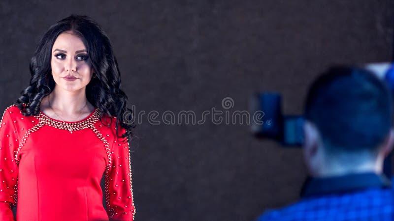 Härlig brunettflicka med långt hår i en röd klänning som poserar till en fotograf i en fotostudio arkivfoton