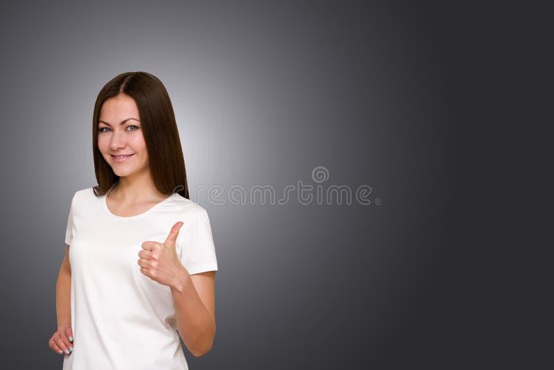 Härlig brunettflicka med långt hår och blåa ögon som visar tummar upp på grå bakgrund arkivfoton