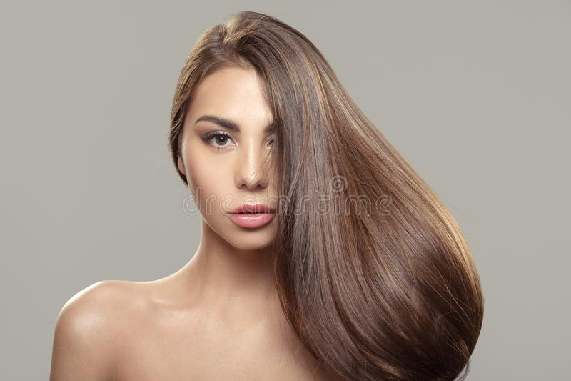 Härlig brunettflicka med långt och rakt brunt hår Skinande slätt hår royaltyfri foto