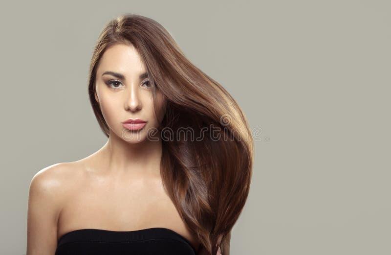 Härlig brunettflicka med långt och rakt brunt hår Skinande slätt hår fotografering för bildbyråer