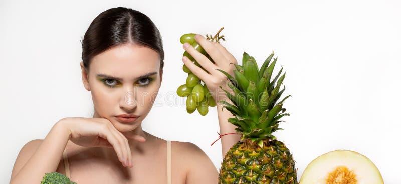 H?rlig brunettflicka med ljus makeup som rymmer gr?na druvor i handen som ser kameran, frukter och gr?nsaker p? arkivbilder
