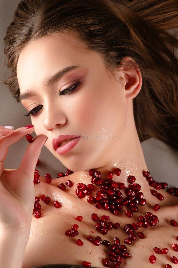 Härlig brunettflicka med rosa frö för makeupinnehavgranatäpple royaltyfri foto