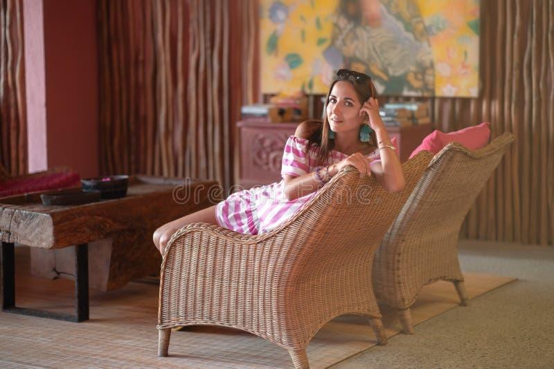 Härlig brunettflicka som sitter i en stol i halva en vänd Inre i etnisk stil royaltyfri bild