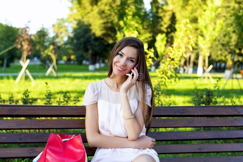 Härlig brunettflicka som talar på telefonen i en parkerasammanträdebänk i klänningen, koppla av för kvinna för affär för sommarda arkivfoton