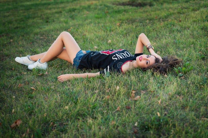 Härlig brunettflicka som vilar på gräsmattagräs En ung ljus tonårig flicka älskar sportar gatamode av den moderna ungdomflickan royaltyfri foto