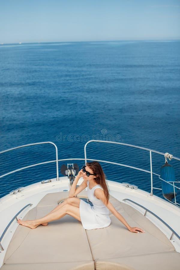Härlig brunettkvinna i den vita klänningen som poserar på fartyget royaltyfria bilder