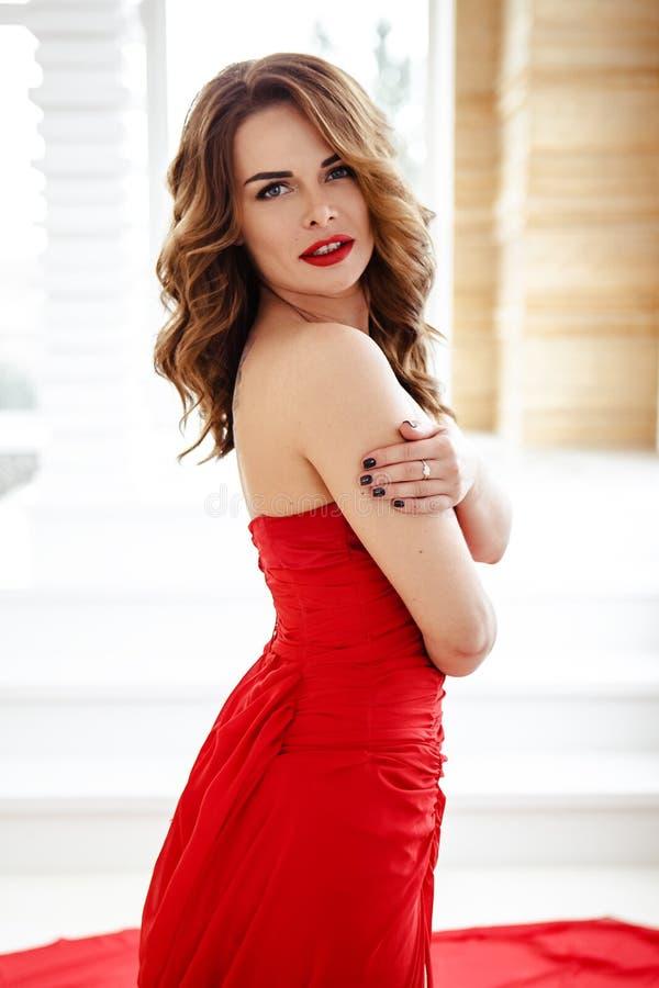 Härlig brunettkvinna i en röd klänning, modeskönhetstående arkivfoto