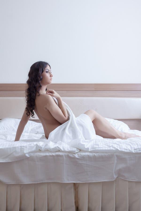 Härlig brunettkvinna i handduk på underlag royaltyfria foton