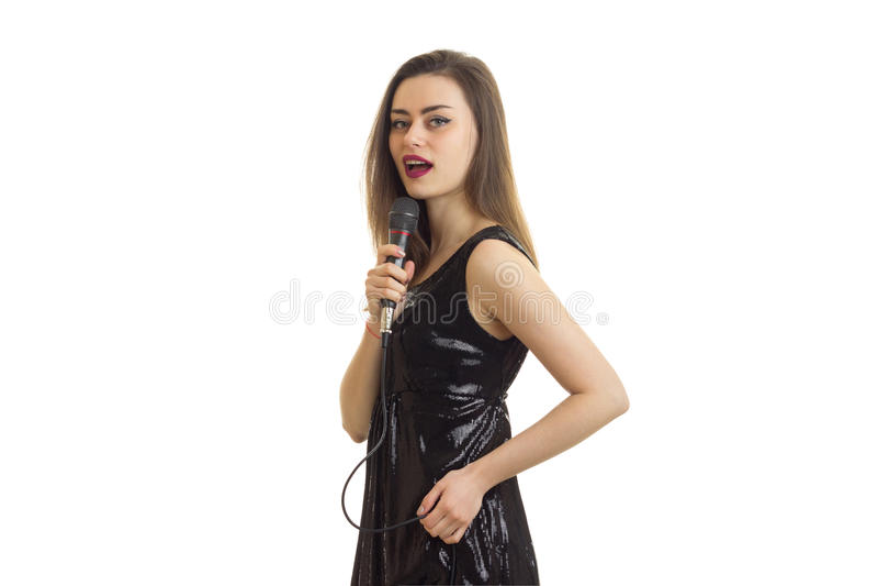 Härlig brunettkvinna i sjungande karaoke för svart klänning fotografering för bildbyråer