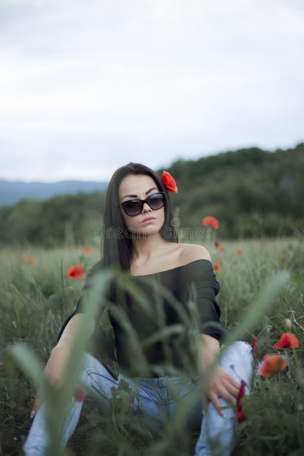 Härlig brunettkvinna i solglasögon och stilfull kläder som sitter bland på röda vallmo royaltyfri bild