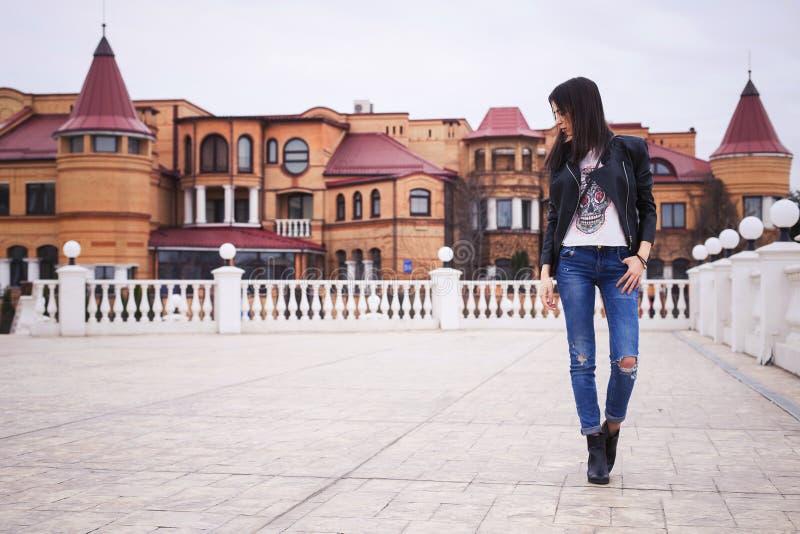Härlig brunettkvinna i svart läderomslag som går på royaltyfria bilder
