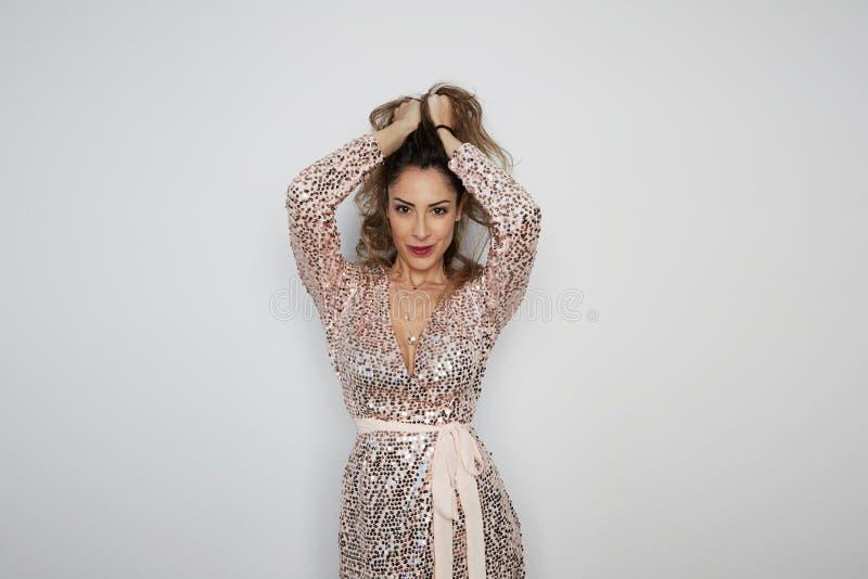 Härlig brunettkvinna i trendig partiklänning Flicka som poserar på pastellfärgat rosa bakgrundsinnehav Glamourstilskönhet royaltyfria bilder